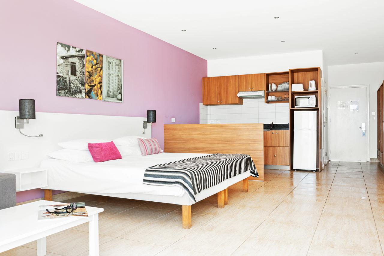 Classic Suite med stor balkon med liggestole og parasol mod poolområdet.